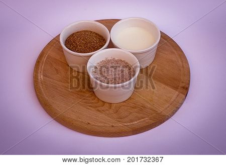 Wheat bran yogurt and mix of them in white bowls on wooden plate