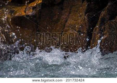 Splashes and drops of river water against a stone background. The river beats against a rocky wall. The background is blurred.