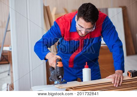 Young repairman working with a power saw sawing