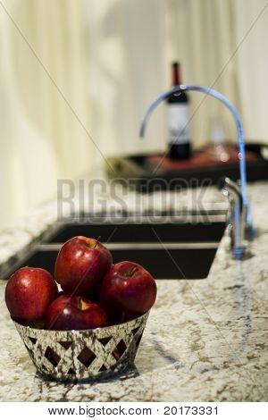 ruby red apples in basket in ultra modern kitchen