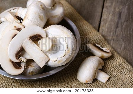 Champignon mushrooms on a wooden background. Close up.