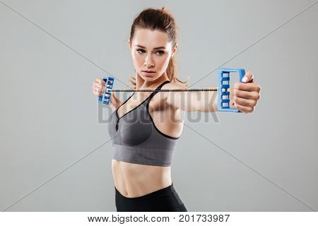 Close up portrait of a confident young fitness woman doing exercises with hand expander isolated over gray background