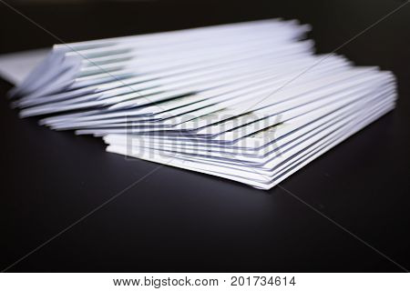 Stack of franked letters in white envelopes on black background