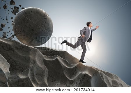 Businessman running away from falling rolling stone