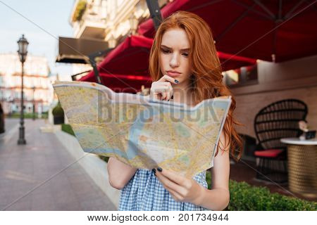 Pensive young redhead girl looking at a guide map while standing outdoors on a city street