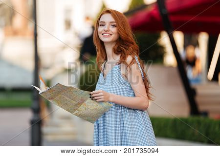 Smiling pretty girl holding a guide map while standing outdoors on a city street