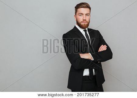 Confident young businessman in suit standing with arms folded isolated over gray background
