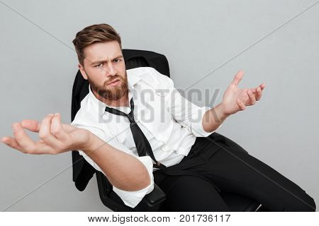 Unsatisfied tired businessman sitting in a chair and gesturing with hands isolated over gray background