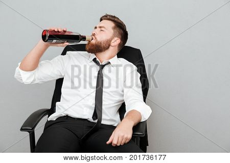 Tired young businessman sitting in office chair and drinking wine from a bottle isolated over gray background