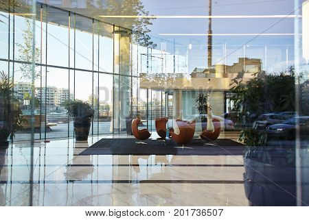 Hotel lounge or modern office interior with leather armchairs. Shot through huge glass window of empty contemporary business center building in the morning. Architecture and design concept