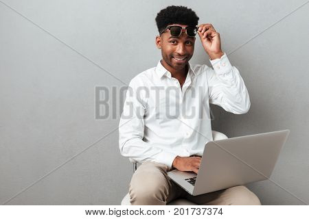 Smiling happy african man holding laptop computer on his lap while sitting in a chair isolated over gray background