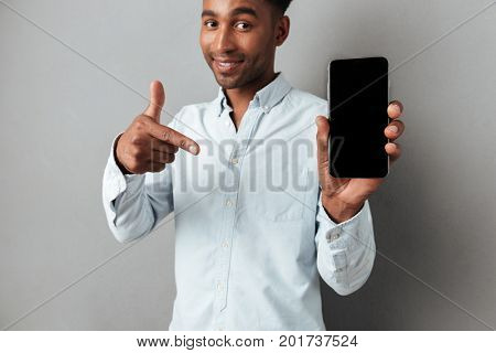 Excited cheerful african man pointing finger at blank screen mobile phone isolated over gray background