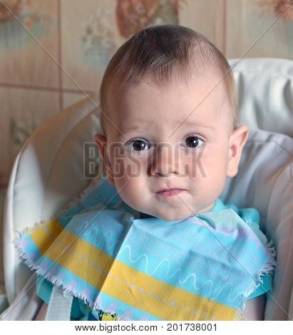 Face of nice quiet baby in bib sitting in highchair