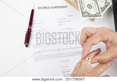 Divorce agreement. Woman taking out wedding ring after the divorce