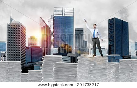 Businessman keeping hand with book up while standing on pile of paper documents with cityscape and sunlight on background. Mixed media.
