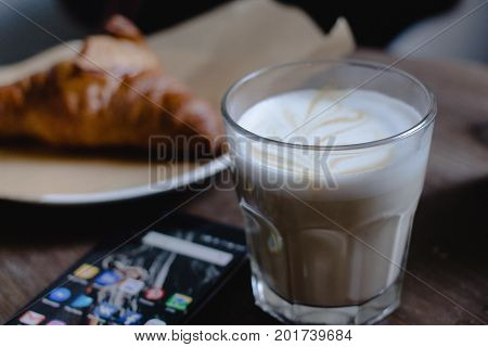 Moscow RUSSIA - August 20th 2017: Latte glass cup with croissant and smartphone One Plus 3T with icons of social media on screen.