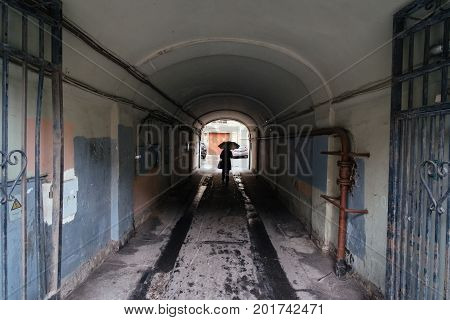 Silhouette of a woman under umbrella walking through little tunnel of an old construction building at a rainy autumn day. City concept at a fall.