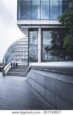 LONDON ENGLAND - JUNE 17 2016: Horizontal picture of a straight line business glass building with a partial view of the City Hall with handrails on both sides and stairs. London.