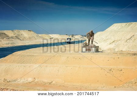 Sinai Egypt - April 2nd 2016: Section of the Suez Canal expansion canal opened in August 2015 with a connecting canal the monument for the suez canal workers and a tugboat in the background