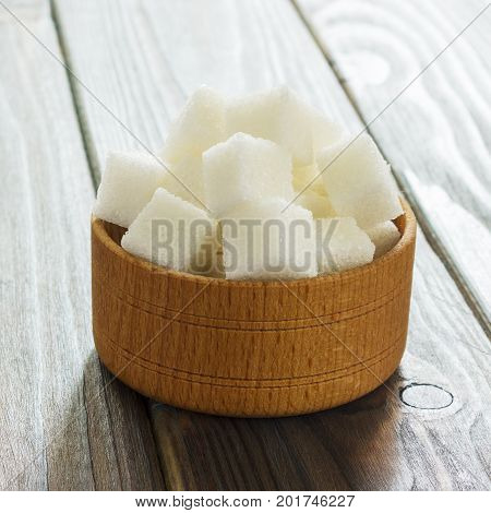 Sugar cubes in bowl on wooden table. White sugar cubes in bowl.