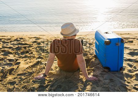 Young caucasian tourist man is standing alone on the beach with a suitcase.