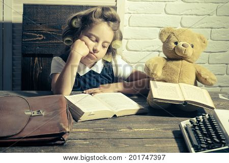 Little baby secretary in cabinet with bear. Kid choose career of journalist or writer. Small girl with curler in hair read book. Child with briefcase and typewriter on table. Education and childhood. poster
