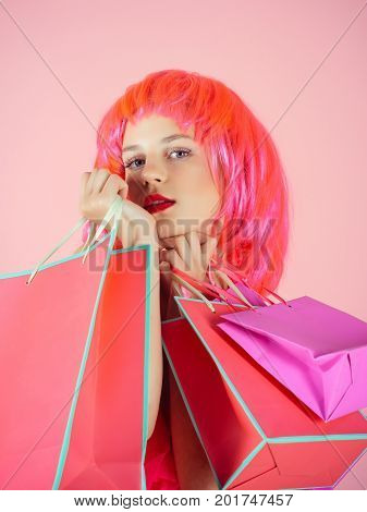 Sale and black friday. Woman with shopping bags. Fashion shopper posing on pink background. Girl wearing red wig. Holidays celebration concept.