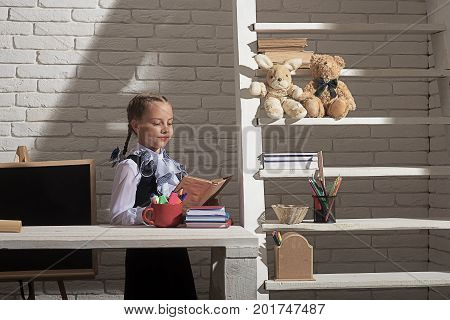 Girl Sits At Desk With Colorful Stationery And Books