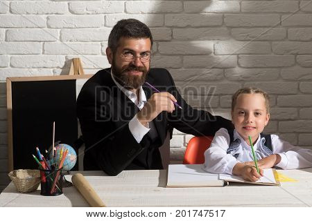 Girl and her father in study room on white brick background. Family sits at desk with school supplies. Schoolgirl and her dad with smiling faces learn to write. Classroom and home education concept
