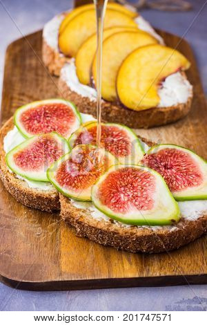 Pouring honey on toasts with cream cheese topped with fresh ripe figs and peaches. Wholegrain rye bran bread on wood cutting board grey concrete background.