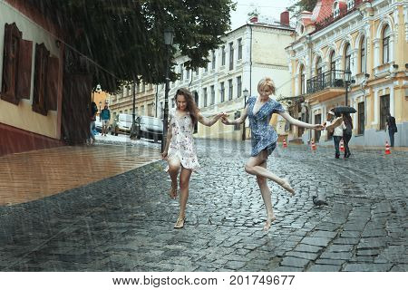Women girlfriends stroll in the rain they cheerfully jump.