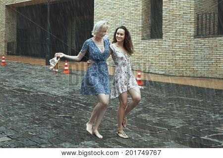 Women are walking in the rain in the city they are smiling and happy.