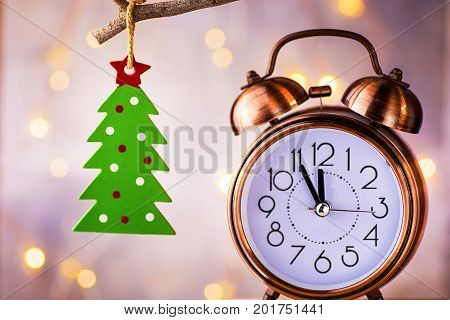 Vintage copper alarm clock showing five minutes to midnight New Year countdown. Green christmas tree ornament hanging on branch. Glittering garland lights.