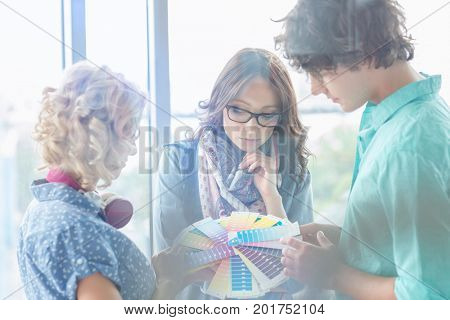 Creative businesspeople analyzing color swatches in office