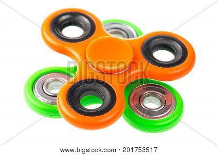 Orange and green fidget spinners close up on each other stress relieving toys isolated on white background