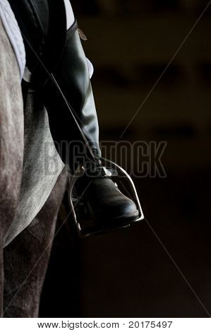 Stirrup and human leg in riding boots poster
