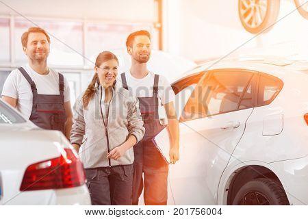 Happy maintenance engineers looking away in automobile repair shop