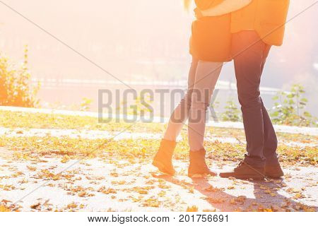 Low section of couple standing in park during autumn