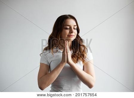 Charming gorgeous young woman with wavy loose hair pressing hands together and closing eyes having pleased smile on her calm face while praying practising yoga or meditating indoors alone