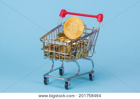 Shopping trolley cart with Coins bitcoin buying goods for crypto currency. Empty space for text