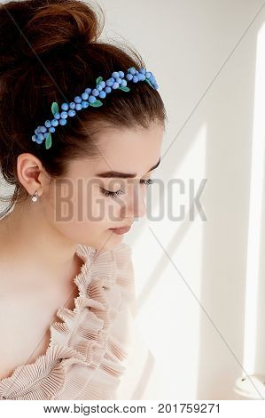 Portrait of beautiful girl with dark hair and light porcelain skin. Hair in a bun. Hair accessory handmade