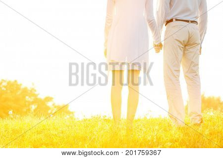 Midsection rear view of couple holding hands on grass against sky