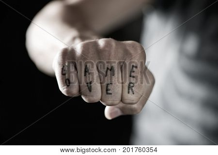 closeup of the hand of a young caucasian man with the text game over written with a temporary ink in his knuckles, with a dramatic effect