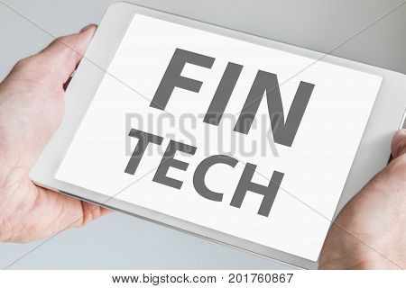 Fin tech text displayed on touchscreen of modern tablet or smart device. Concept of financial technology startup company.