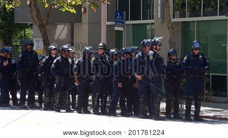 Berkeley CA - August 27 2017: Police in riot gear standby as the €œNO TO MARXISM IN AMERICA€ rally in Martin Luther King Jr. Civic Center Park proceeds more counter-protesters than protesters.