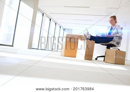 Full length of young businesswoman using laptop with feet up on moving box in office