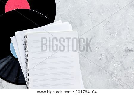 dj work set with notes and vynil records on stone table background top view mock up