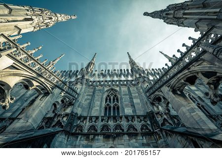 The roof of the Milan Cathedral (Duomo di Milano) in Milan, Italy. Milan Duomo is the largest church in Italy and the fifth largest in the world. Low angle view.