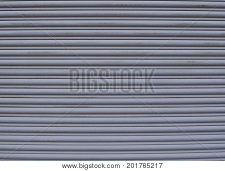 A gray serrated metal garage door with multiple rows