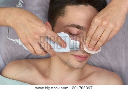 Ultrasonic face cleaning, young male. Hands of cosmetologist working.